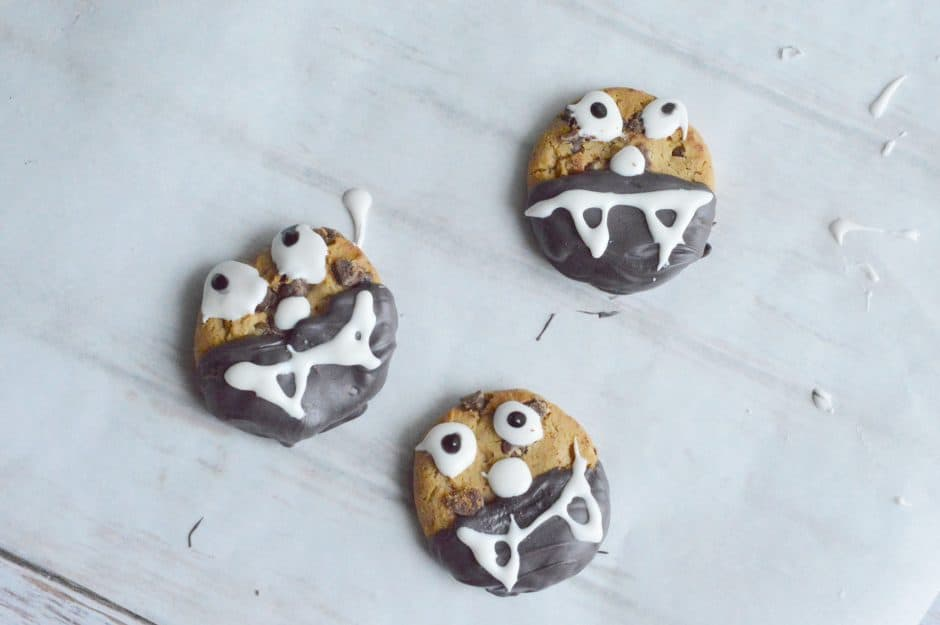 photo of chocolate chip cookies dipped in brown chocolate icing and white frosting eyes and fangs