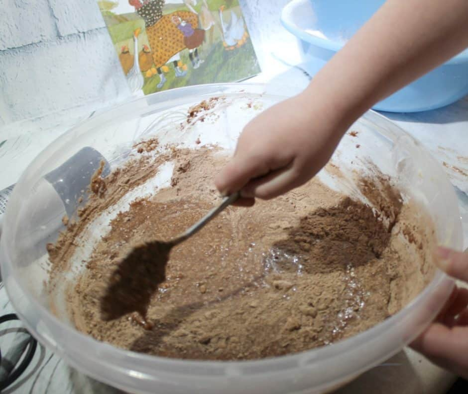 Child making chocolate Thunder Cake with book in the background mixing wet and dry ingredients