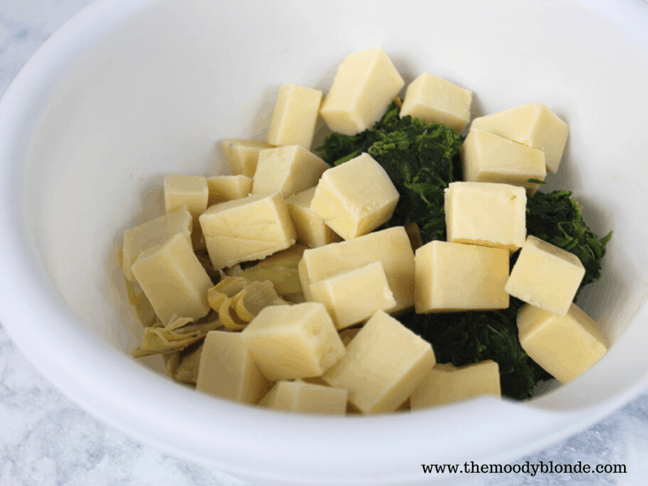 White bowl on marble background with spinach, artichoke hearts, and chunks of cheddar in it